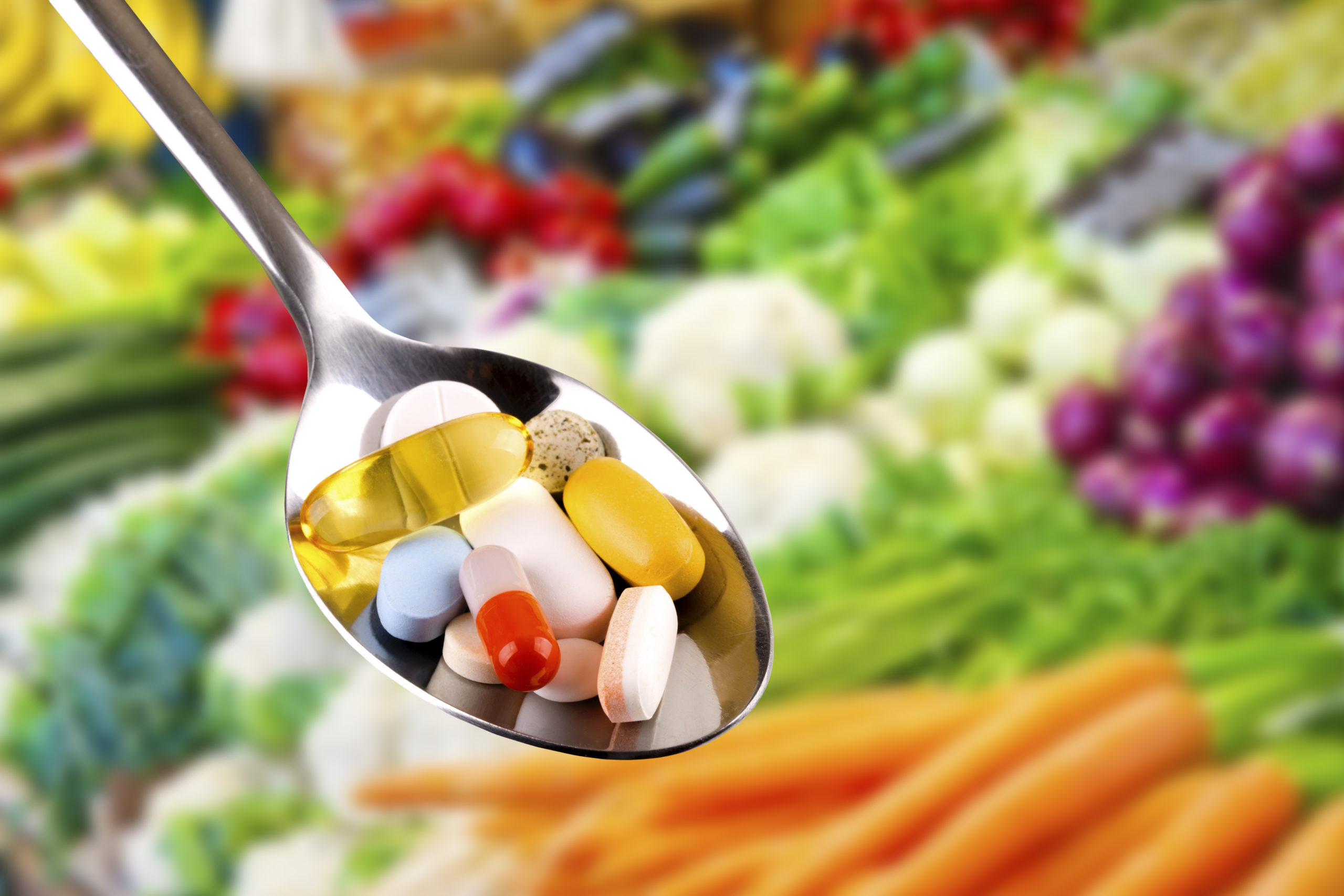 Spoon with pills, dietary supplements on vegetables background.