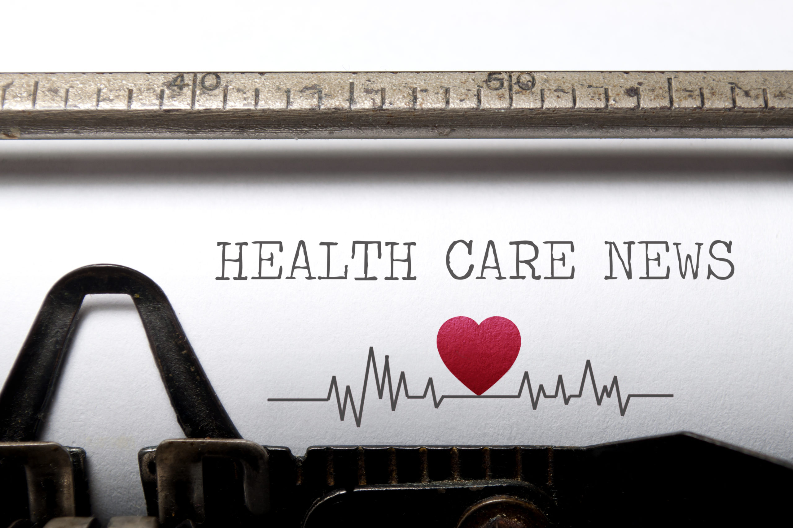 Health care news printed on an old typewriter with heart beat pulse sketch.
