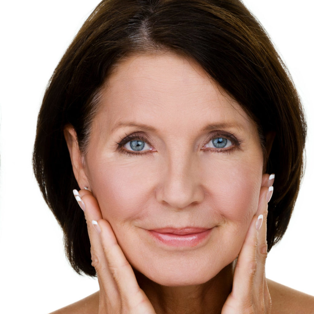 Mature woman holding face.