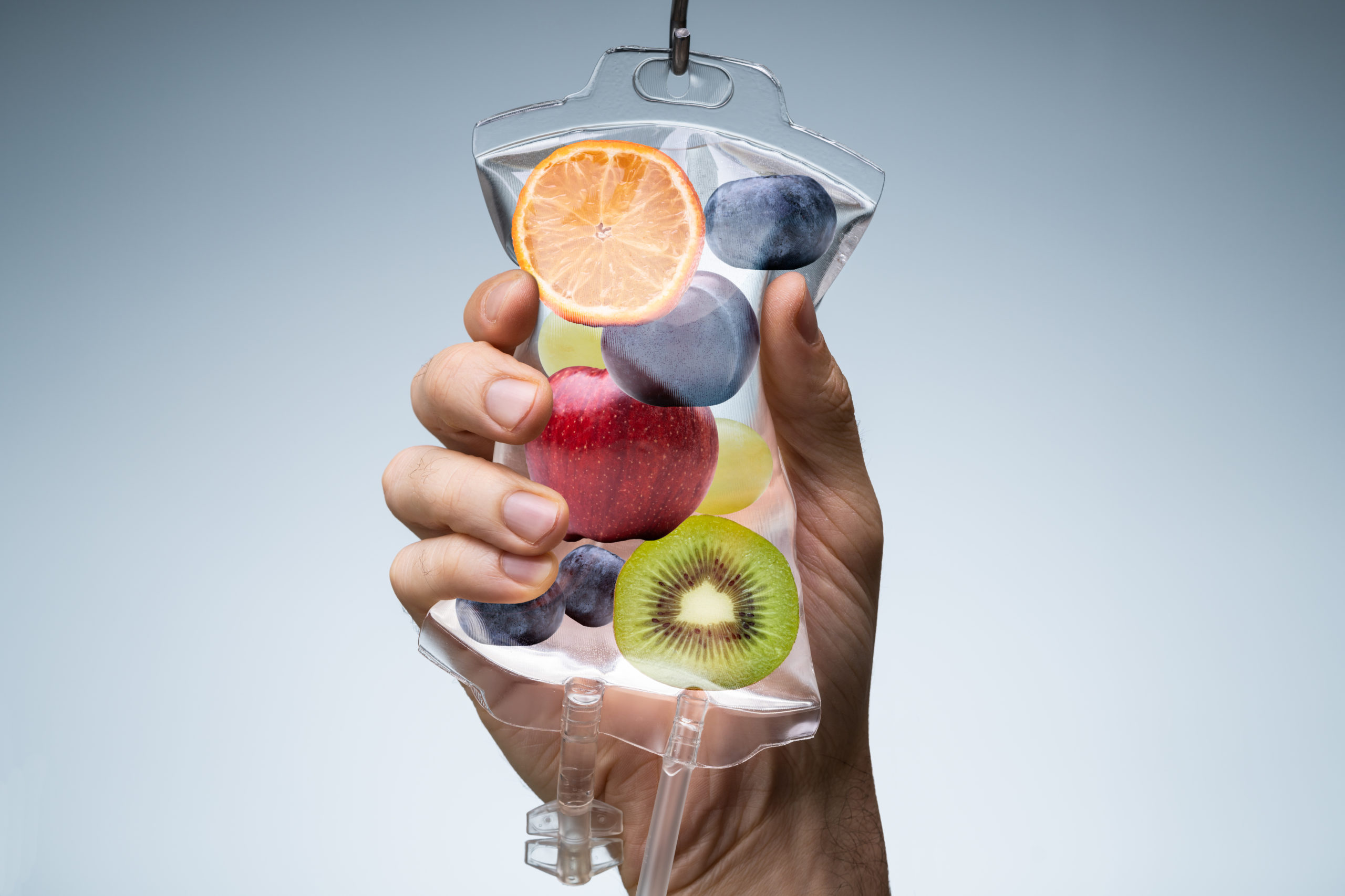 Hand holding saline bag with fruit.