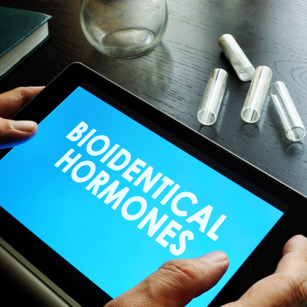 doctor holding tablet that says bioidentical hormones
